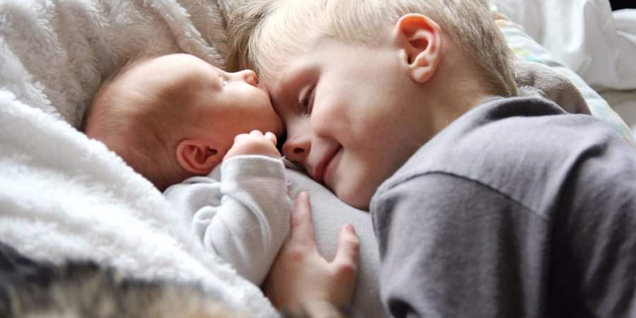 child hugging new sibling baby